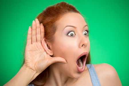 chitchat: Closeup portrait young nosy woman hand to ear gesture shocked carefully intently secretly listening on juicy gossip conversation news privacy violation isolated green background. Human face expression