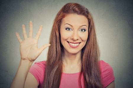 five fingers: Closeup portrait, young excited woman, making five times sign gesture with hand fingers, isolated grey wall background. Positive human emotion facial expression feeling, attitude, symbol body language Stock Photo