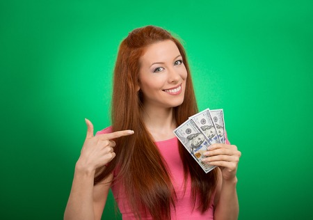 employee satisfaction: Closeup portrait super happy excited successful young business woman holding money dollar bills in hand isolated on green background. Positive emotion facial expression feeling. Financial reward