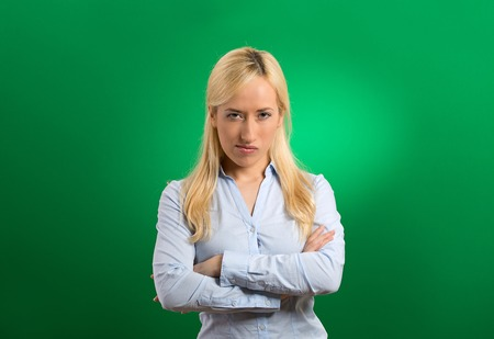 enrage: portrait angry blonde woman on green background