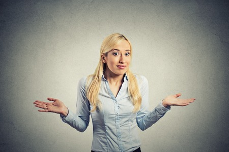 i dont know: Portrait  young woman arms out shrugs shoulders asking who cares so what I dont know isolated grey wall background. Negative human emotion, facial expression body language life perception attitude