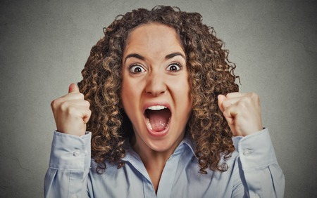 complaining: Closeup portrait headshot angry young woman having nervous breakdown screaming isolated grey wall background. Negative human emotion facial expression feeling attitude