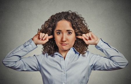 loud noise: Closeup portrait young angry, unhappy woman covering closed ears looking at you annoyed by loud noise giving her headache ignoring isolated grey wall background. Negative emotion perception attitude