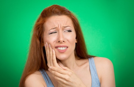 negative area: Closeup portrait young woman with sensitive toothache crown problem about to cry from pain touching red area outside mouth with hand isolated green background. Negative emotion face expression feeling
