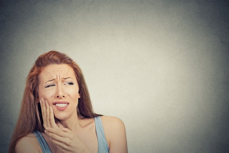 amalgam: Closeup portrait young woman with sensitive tooth ache crown problem about to cry from pain touching outside mouth with hand isolated grey background. Negative emotion face expression feeling