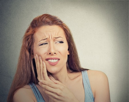 root canal: Closeup portrait young woman with sensitive tooth ache crown problem about to cry from pain touching outside mouth with hand isolated grey background. Negative emotion face expression feeling
