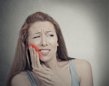 negative area: Closeup portrait young woman with sensitive tooth ache crown problem about to cry from pain touching red area outside mouth with hand isolated grey background. Negative emotion face expression feeling