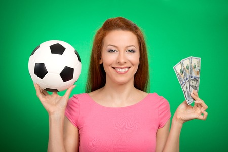winning bid: Football and money. Young attractive woman holding soccer ball and cash isolated on green background. Competition lottery gambling concept idea