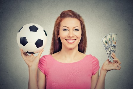 winning bid: Football and money. Young attractive woman holding soccer ball and cash isolated on grey wall background. Competition lottery gambling concept idea Stock Photo