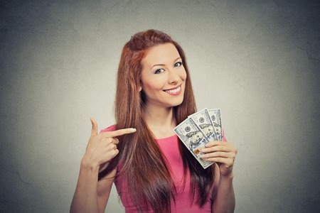 expression: Closeup portrait super happy excited successful young business woman holding money dollar bills in hand isolated grey wall background. Positive emotion facial expression feeling. Financial reward