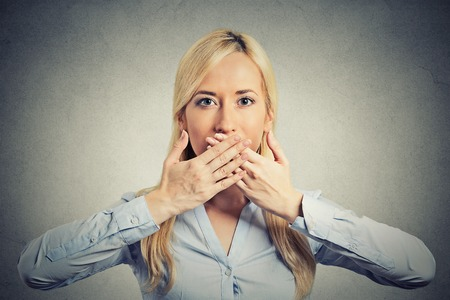 closed mouth: Closeup portrait young woman covering closed mouth with hands open eyes. Speak no evil concept isolated grey wall background. Human emotion facial expression sign symbol. Social media news coverup Stock Photo
