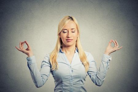 Retrato feliz mujer de negocios joven en camisa azul ojos cerrados las manos levantadas en la meditación relajante aire toman aislado respiración profunda fondo de la pared gris. Estilo de vida empresarial. Técnica de alivio de tensión Foto de archivo