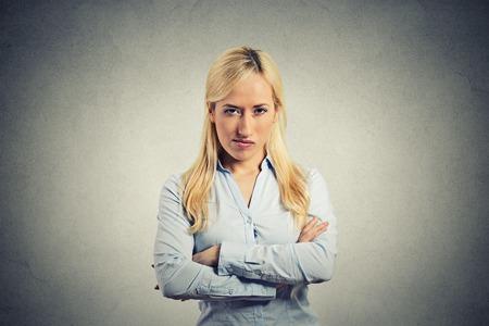 portret boze blonde vrouw op een grijze achtergrond