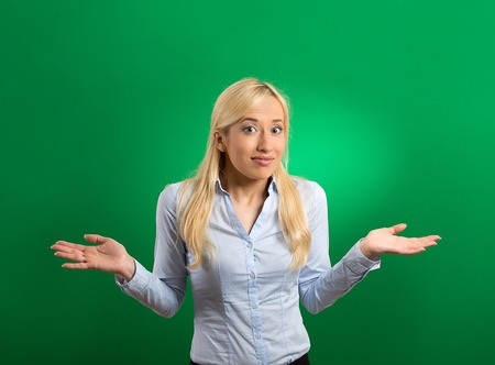 disinterest: Portrait young woman arms out shrugs shoulders asking who cares so what I dont know isolated green background. Negative human emotion, facial expression body language life perception bad attitude Stock Photo