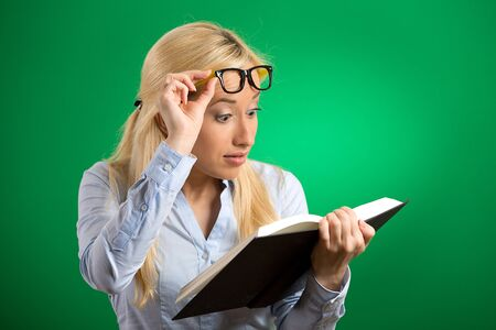 nearsighted: Closeup portrait headshot young woman wide opened eyes looking at book page shocked surprised by twists turn of story isolated green background. Human emotion facial expression feeling reaction