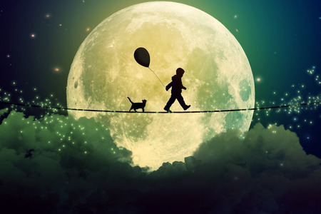 Happy boy teenager and cat walking with balloon on a tight rope above clouds with moonlight moon background. Happiness care free concept.  Stok Fotoğraf