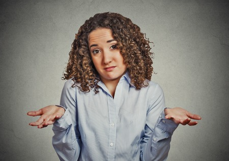 body expression: Portrait dumb young woman arms out shrugs shoulders who cares so what I dont know isolated grey wall background. Negative human emotion, facial expression body language life perception attitude