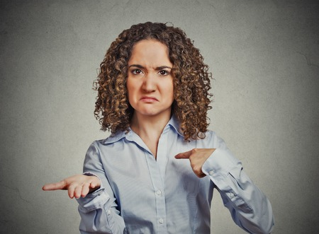 Closeup portrait young woman gesturing with hand palms up to pay back now bills money isolated grey wall background. Negative human emotion facial expression feeling reaction body language