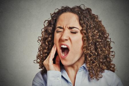 gencives: Gros plan portrait jeune femme avec dent sensible problème de la couronne de douleurs sur le point de pleurer de douleur toucher la bouche avec la main en dehors isolé gris mur arrière-plan. Émotion négative sentiment d'expression du visage