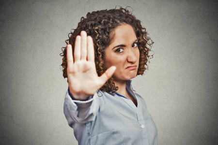 woman stop: Closeup portrait young annoyed angry woman with bad attitude giving talk to hand gesture with palm outward isolated grey wall background. Negative human emotion face expression feeling body language