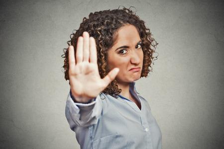 Gros plan portrait jeune femme en colère ennuyé avec mauvaise attitude donnant parler geste de la main avec la paume vers l'extérieur isolé gris mur arrière-plan. Négatif visage émotion langage corporel de sentiment de l'expression humaine