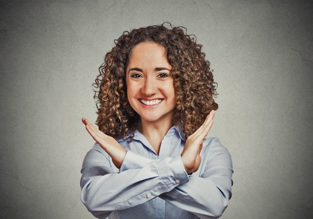 nonverbal communication: Happy smiling young woman making showing stop gesture isolated on grey wall background. Human emotion facial expression feelings, signs symbols, body language, reaction, nonverbal communication