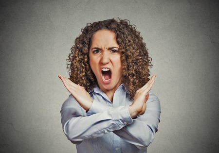 nonverbal communication: Angry screaming young woman making showing stop gesture isolated on grey wall background Negative human emotion facial expression feelings, sign symbol body language, reaction nonverbal communication Stock Photo