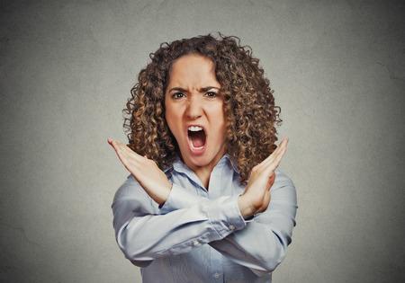 comunicacion no verbal: Enojado gritando mujer joven que hace mostrando parada gesto aislado en el fondo de la pared gris negativos emoci�n humana sentimientos de expresi�n facial, signo simbolo lenguaje corporal, reacci�n comunicaci�n no verbal Foto de archivo