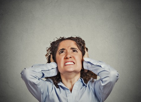 loud noise: Closeup portrait young angry unhappy stressed woman covering her ears looking up stop making loud noise its giving me headache isolated grey wall background. Negative emotion face expression feeling Stock Photo
