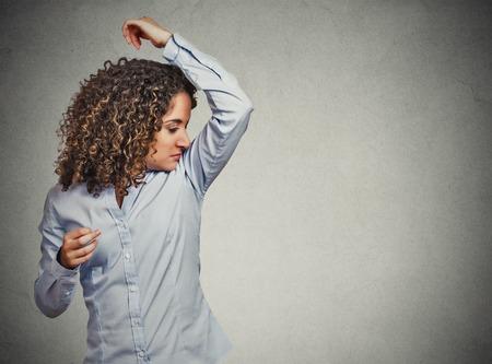 Retrato del primer mujer joven, oliendo, oliendo su axila mojado, algo huele mal, muy mala situación mal olor aislados fondo gris de la pared. Emoción humana expresión facial sentimiento Reacción negativa Foto de archivo