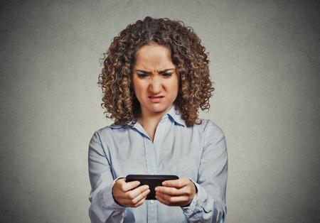 problemas familiares: Retrato del primer trastorno triste escéptico mensajes de texto hablando mujer seria infeliz en el teléfono desagradó disgustado con la conversación aislado fondo de la pared gris. Emoción humana sentimiento expresión de la cara negativa