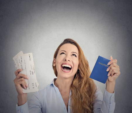 Portrait happy excited tourist young woman holding passport holiday flight ticket looking up isolated grey wall background. Positive human emotion face expression. Travel vacation getaway trip concept photo