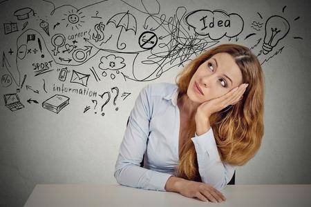 mente humana: Mujer de negocios sentado en la mesa tiene muchas ideas de cosas que hacer la planificaci�n de futuro aislado fondo gris pared de la oficina. Percepci�n de la carrera. Personal concepto de equilibrio trabajo vida. Proceso de toma de decisiones Foto de archivo