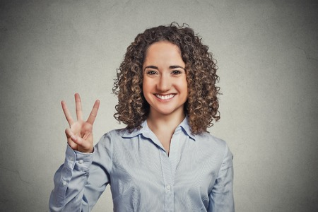 Closeup portrait young curly hair woman giving three fingers sign gesture isolated grey wall background. Positive human emotion facial expression feeling symbol body language non verbal communication