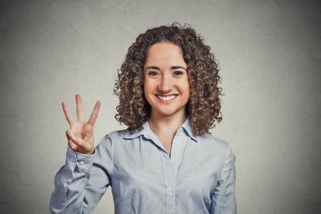 Ritratto del primo piano giovane donna, capelli ricci dando tre dita segno gesto isolato sfondo grigio muro. Emozione umana espressione del viso sentimento simbolo linguaggio del corpo positivo la comunicazione non verbale Archivio Fotografico - 36184732