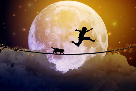 Happy boy teenager and cat jumping with balloon on a tight rope above clouds with moonlight moon background. Happiness care free concept.