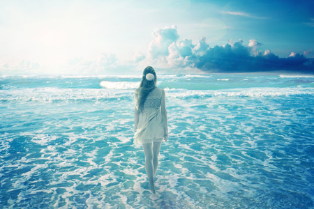 Young woman walking on a dreamy beach enjoying ocean colorful blue sky view. Landscape nature screen saver photo
