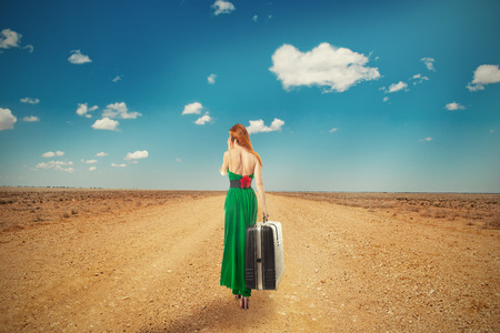 Beautiful woman walking through a desert road talking on mobile phone carrying big suitcase isolated on blue cloudy sky background. Embrace challenge unknown new life loneliness concept. Long journey Stock Photo
