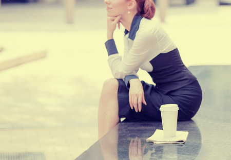 mid life: Side profile lonely woman sitting outside corporate office selective focus on cup of coffee