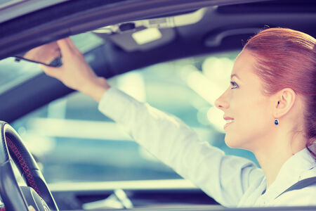 traffic rules: Happy young woman driver looking adjusting rear view car mirror, making sure line is free visibility is good before making turn. Human facial expressions, emotions. Safe trip, journey driving concept
