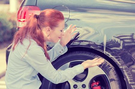 Gefrustreerde jonge vrouw de controle op wijzend op auto krassen en deuken outdoors Stockfoto