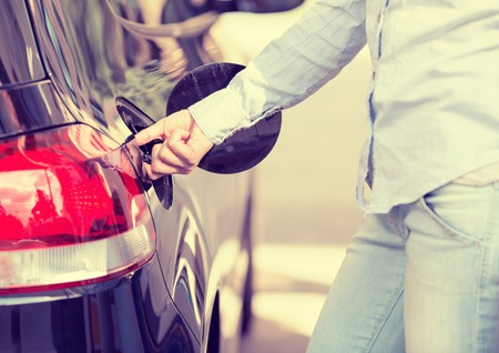Woman opening car gas tank cap at petrol station Stock Photo - 36468057