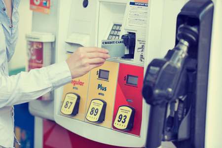 Woman hand swiping credit card at gas pump station. Banque d'images