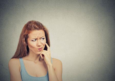 lenguaje corporal: Foto de cabeza pensativa escéptica mujer joven sospechoso sobre fondo gris Foto de archivo