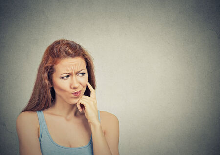 confused: Headshot thoughtful skeptical suspicious young woman on grey background Stock Photo
