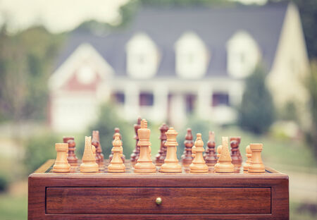 savings risk: Real estate sale, home savings, loans market concept. Housing industry mortgage plan and residential tax saving strategy. Chess game figures isolated outside home background. Focus on desk. Homeowner Stock Photo