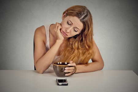 relationship breakup: Sad depressed young woman sitting at table drinking coffee looking at her mobile phone waiting for a call text message isolated on grey wall background. Stock Photo