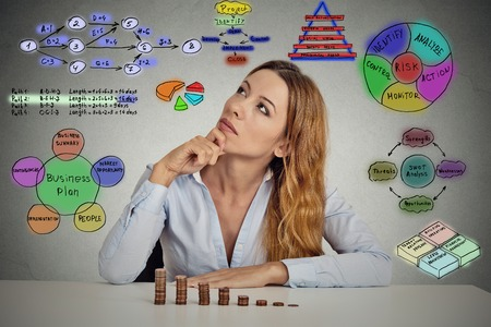 mutual funds: Manager businesswoman sitting at table thinking has idea calculating risks of new project implementation plan sketch formulas charts written on grey wall background. Leadership concept