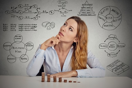 Manager businesswoman sitting at table thinking has idea calculating risks of new project implementation plan sketch formulas charts written on grey wall background. Leadership concept