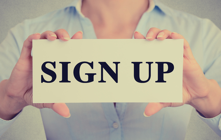 signup: Closeup businesswoman hands holding white card sign with sign up text message isolated on grey wall office background. Retro instagram style image